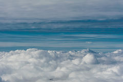Grey cloud cover seen from above aginst blue sky horizon Royalty Free Stock Images