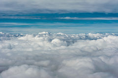 Grey cloud cover seen from above aginst blue sky horizon royalty free stock photography