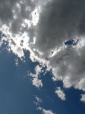 GREY CLOUDS. ON DARK BLUE SKY ILLUMINATED  BY THE SUN Royalty Free Stock Photos