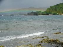 Cloudy sky and rainbow over the tropical island Royalty Free Stock Photos