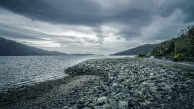 Grey clouds over a lake in Scotland, Europe. Royalty Free Stock Photos
