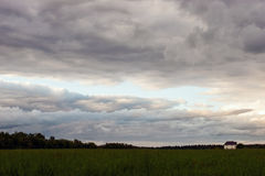 Grey clouds overs the field with a single house Royalty Free Stock Image