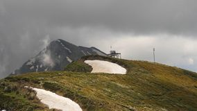 Grey clouds passing at mountain peak, timelaps stock photo