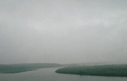 Grey cloudy sky on river. And green fields stock photos