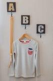 Grey color boy's shirt hang on wall Royalty Free Stock Image