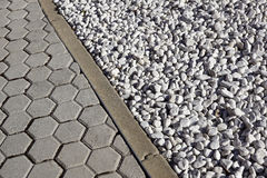 Grey colored round stones next to a concrete curb Stock Photos