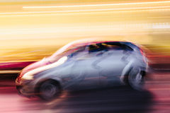 Grey Compact Car in a Blurred City Scene Royalty Free Stock Image