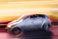 Grey Compact Car in einer unscharfen Stadt-Szene Lizenzfreies Stockbild