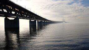 Grey Concrete Bridge on Body of Water Under Blue and White Sky during Daytime Royalty Free Stock Photography