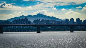 Grey Concrete Bridge Near Cities and Mountain at Daytime Stock Images