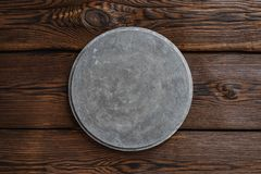 Grey concrete round signboard on wooden brown background stock photography