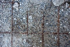 Grey concrete surface with visible reinforcement and crushed stones stock photos