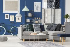 Grey corner couch in room. Patterned pillows on grey corner couch and metal tables in living room interior with bike, screen and posters Stock Images