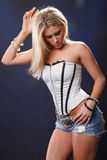 Grey corset. Cute blond in jeans and corset Royalty Free Stock Image