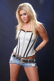 Grey corset. Cute blond in jeans and corset Stock Image
