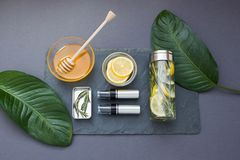 Grey cosmetic composition with honey and lemon. Top view. Dark grey cosmetic frame with honey, mango,  and lemon. Top view Stock Photo