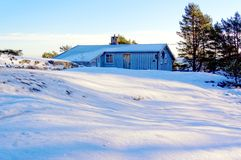 Grey cottage  in a snow forest Royalty Free Stock Image