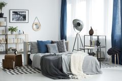 Grey cozy bedroom interior. Grey bedding on bed in cozy bedroom interior with lamp and plants on shelves with books stock image