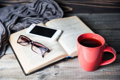 Grey cozy knitted scarf with cup of coffee or tea, phone, glasses and open book on a wooden table. Royalty Free Stock Image