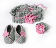 Grey crochet baby booties and headband with. Pink flowers Stock Image