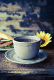 Grey cup of tea on a wooden table against the background of a baguette and sunflower. Grey cup of tea on wooden table against the background of a baguette and stock image