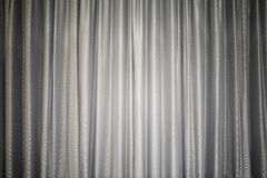 Light gray fabric curtain closed like on a theater show stage, with light in the middle, background, texture Stock Image