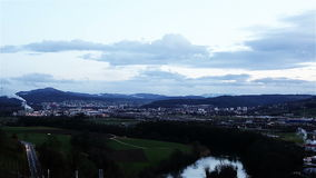 Grey dark clouds are flying low above the ground on a blue sky background. Switzerland, Zurich. City during sunset. Green field and gray road with cars under stock video footage