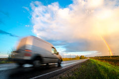 Grey delivery/cargo van going fast on a highway. Grey delivery, cargo van going fast on a highway. Landscape with country road and rainbow Stock Photo