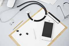 Grey desktop with empty cellphone. Top view of grey doctor`s workplace with empty cellphone, paperwork, stethoscope and other items. Mock up, 3D Rendering Stock Images