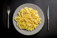Grey dish full of penne pasta  on a black background Stock Photography