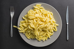 Grey dish full of penne pasta isolated on a black background Royalty Free Stock Image