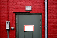 Grey door on red wall Royalty Free Stock Photo