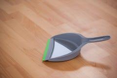 Grey dustpan on wooden floor Stock Photos