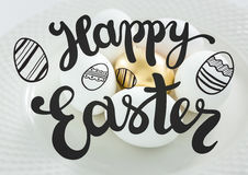 Grey easter graphic against white and gold eggs on plate Royalty Free Stock Image