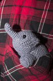 Grey elephant crocheted sitting in plaid shirt pocket. Little grey elephant crocheted sitting in a pocket shirt with red, black and white cage stock image