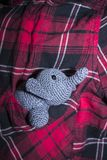Grey elephant crocheted sitting in plaid shirt pocket. Little grey elephant crocheted sitting in a pocket shirt with red, black and white cage stock photography