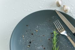 Grey empty ceramic plate with herbs knife and fork on salty white background. Minimal design. Space for text. Or menu royalty free stock photos
