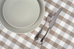 Grey empty plate with vintage fork and knife on beige checkered tablecloth. Royalty Free Stock Photo