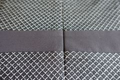 Grey fabric with brown stripe from above. Grey fabric with dark brown stripe from above Stock Photo