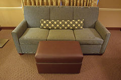 Grey Fabric Sofa avec le tabouret de cuir de Brown et le long oreiller étroit Photos stock