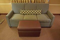 Grey Fabric Sofa med den bruna läderottomanen och begränsar länge kudden Arkivfoton