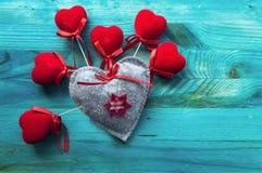 Grey felt heart and many red velvet hearts stock photos