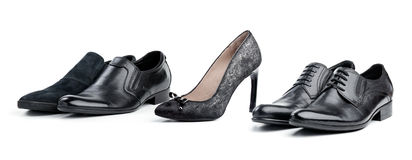 Grey female shoe between black male shoes. Over white background Royalty Free Stock Photos