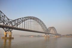 Metallic bridge in fog. Grey foggy light on the Irrawaddy River or Ayeyarwady River in Myanmar. Metallic bridge in the foreground at golden hour Royalty Free Stock Image