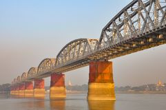 Burn the bridge. Grey foggy light on the Irrawaddy River or Ayeyarwady River in Myanmar. Stoupas in the background, metallic bridge in the foreground at golden Stock Photos