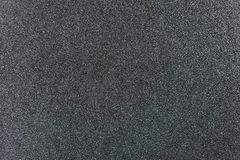 Grey Glitter Background. Charcoal grey colored sand paper textured background with sparkles and glitters stock photography