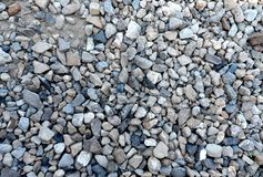 Grey gravel covers a grey clay soil royalty free stock images
