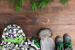 Grey and green winter street wear clothes with dri tree decorati. On over brown wooden background with copy space, flat lay Royalty Free Stock Photo