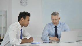 Grey Hair Businessman Explaining Project durante a reunião sobre o portátil ao homem de negócios africano vídeos de arquivo