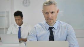 Grey Hair Businessman Looking en la cámara en oficina almacen de metraje de vídeo